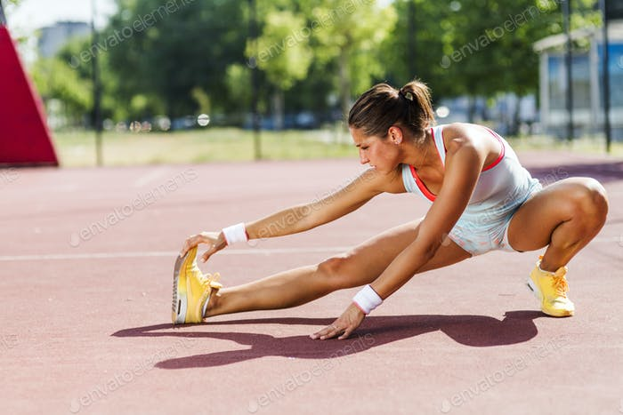 Beautiful young athletic woman stretching in summer