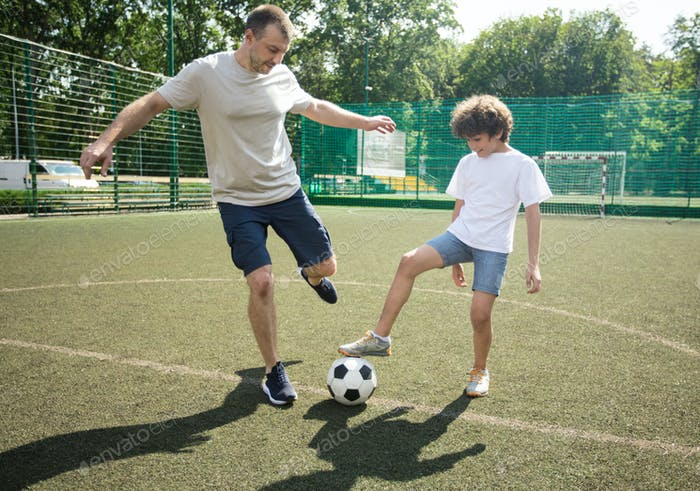 Sportive dad playing soccer with his son