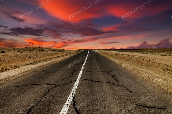 Picturesque fiery sunset over the cracked desert road