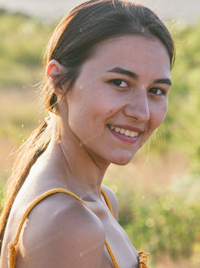 Portrait of young brunette woman posing in summer field in yellow dress. Mountain background view.