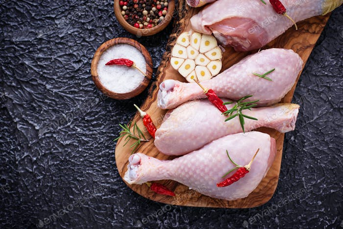 Raw chicken legs with spices and garlic.
