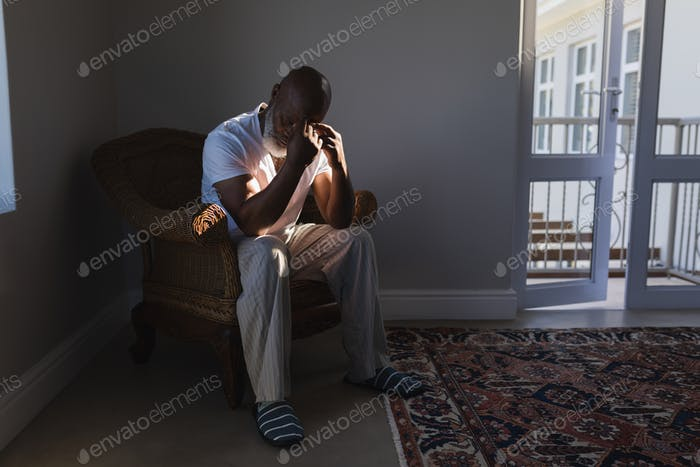 Front view of a worried senior African American man sitting on wicker chair in living room at home