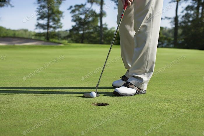 Golfer taps in a putt on a golf green