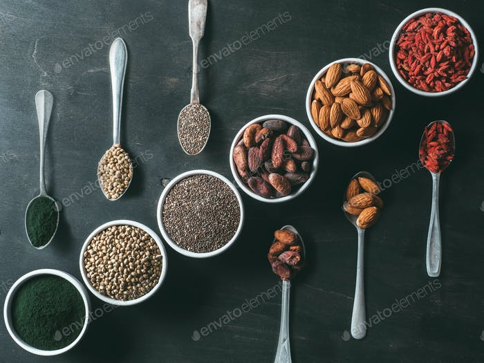 Various superfoods on black wooden table