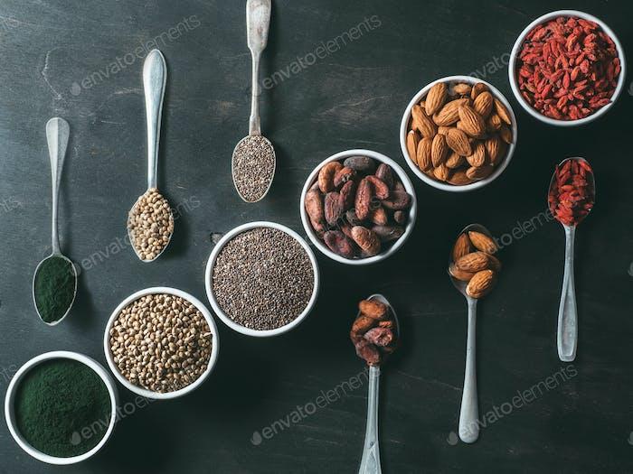 Verschiedene Superfoods auf schwarzem Holztisch