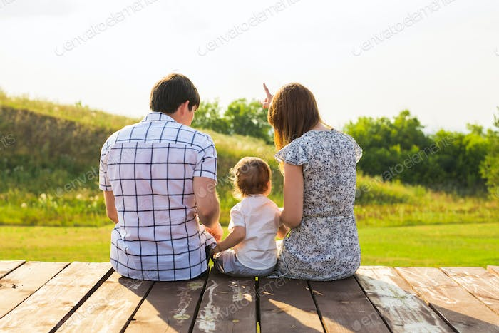 Rear view of mother, father and son sitting together outdoors