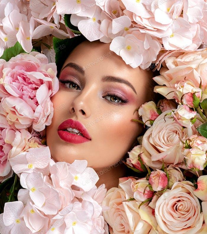 Schönes weißes Mädchen mit Blumen.