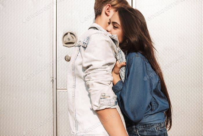 Young beautiful couple in love cheerfully hugging with gray trailer on background