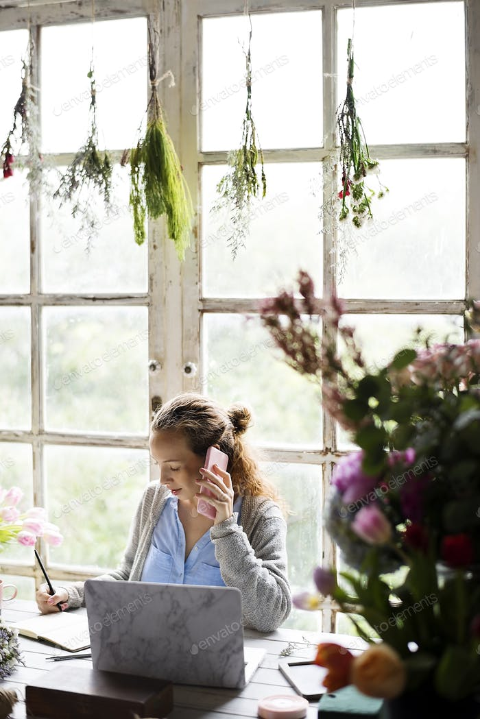 Woman Talking on Mobile Phone in Flower Shop