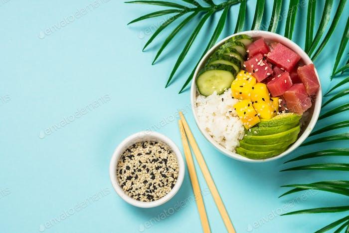Thunfischschüssel mit Reis, Avocado, Mango und Gurke auf blau