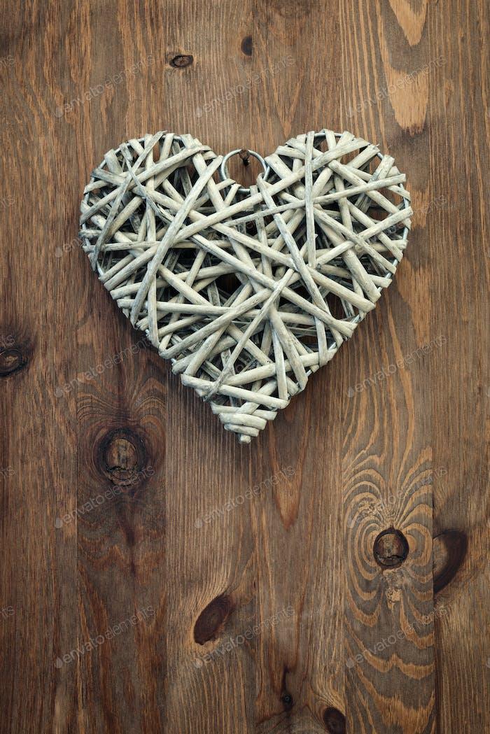 Schilfherz hängt an einem rustikalen Holzhintergrund.
