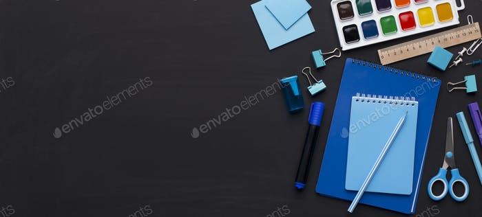 Blue colored school stationery on black board with copy space