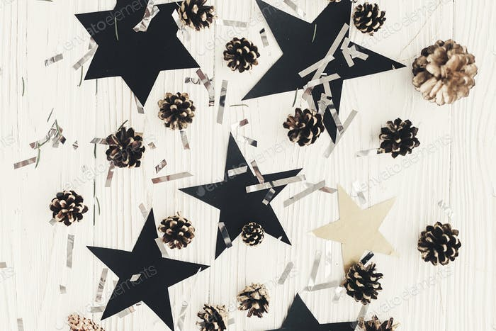 Christmas layout with golden pine cones, silver confetti, black stars on white wood
