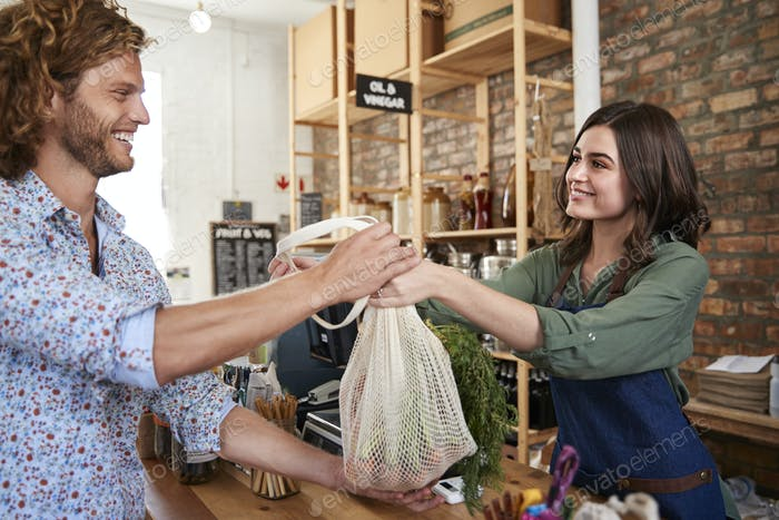 Customer Paying For Shopping At Checkout Of Sustainable Plastic Free Grocery Store