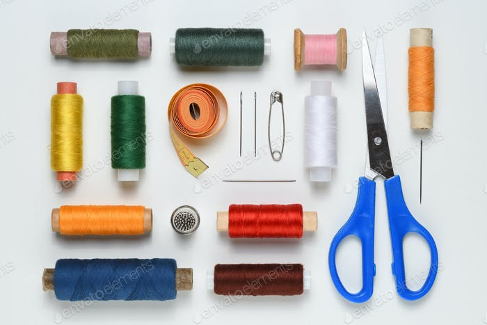 Sewing accessories on white table flat lay