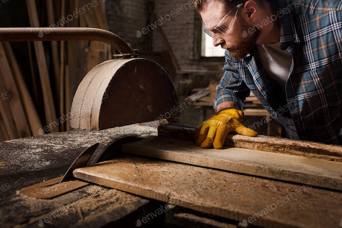 cropped shot of bearded carpenter in protective gloves and googles using machine saw at sawmill