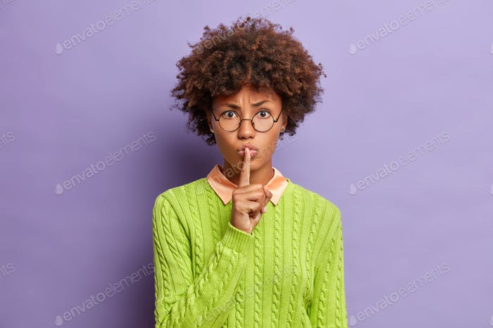 Mysterious serious young Afro American woman makes silence gesture has displeased expression presses