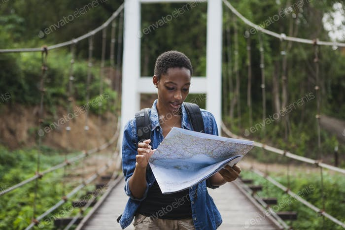 African American woman looking at a map travel and explore concept