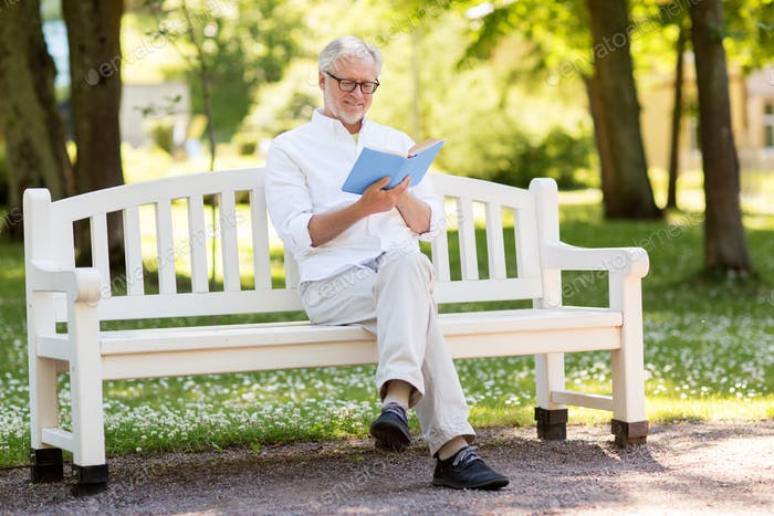 happy senior man reading book at summer park