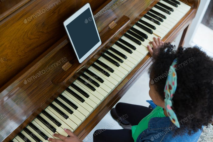Girl playing piano with digital tablet