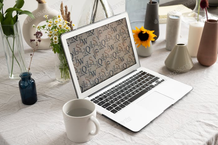 Workplace of businessperson or creative designer with laptop and mug with water