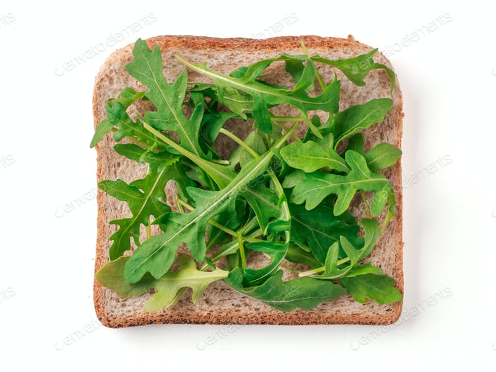 Bread slice with arugula leaves isolated on white