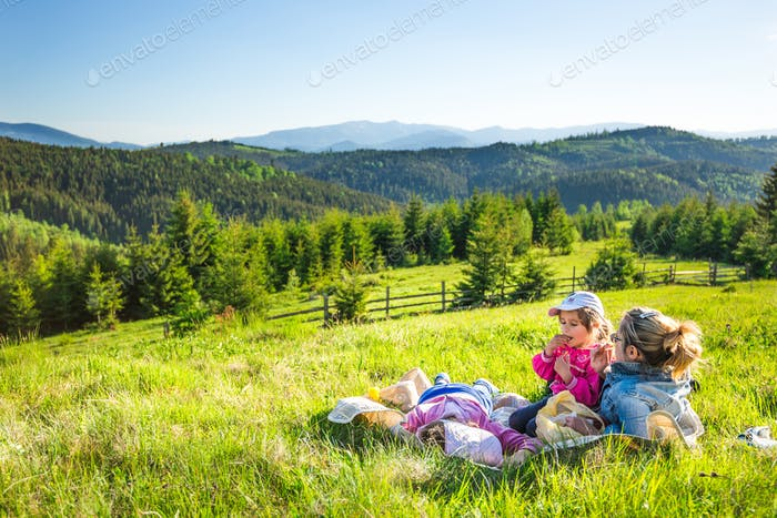 Young mother and little daughters on a slope overgrown with grass