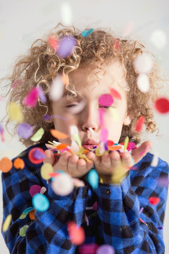 Boy blowing confetti