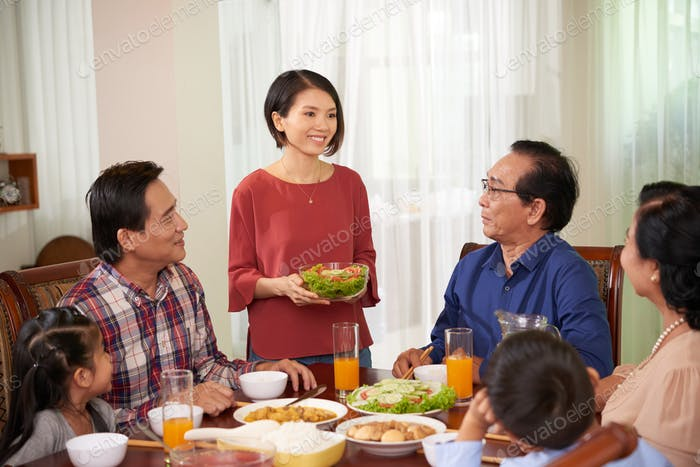 Housewife bringing dish to table