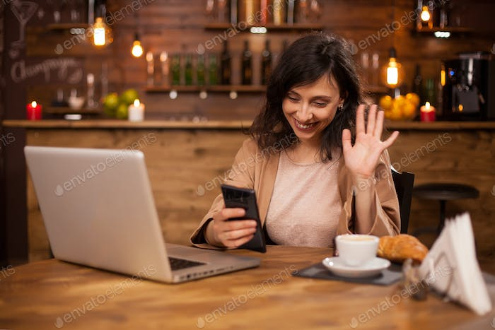 Portrait of beautiful business woman waving at her phone during a video call in a coffee shop