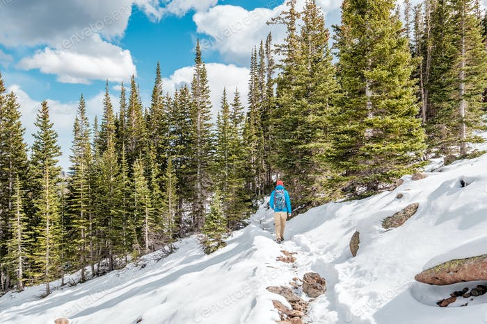 Tourist with backpack hiking on snowy trail