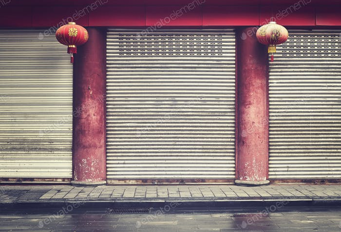 Closed shop facade with red columns and lanterns, China.