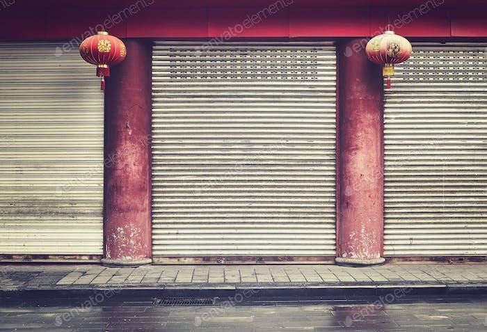 Fachada de la tienda cerrada con columnas rojas y linternas, China.