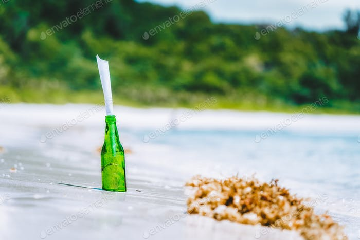 Bottle with message on white paradise sandy beach with blurred jungle in background conceptual
