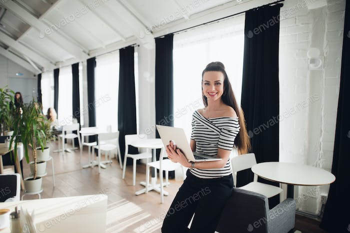 Young Caucasian woman smiling and looking at camera and using laptop in cafe.