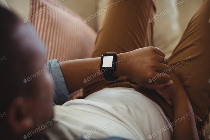 Man lying on sofa and checking his smartwatch