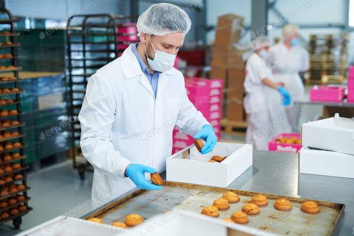 Confectionery factory worker packing pastry into box