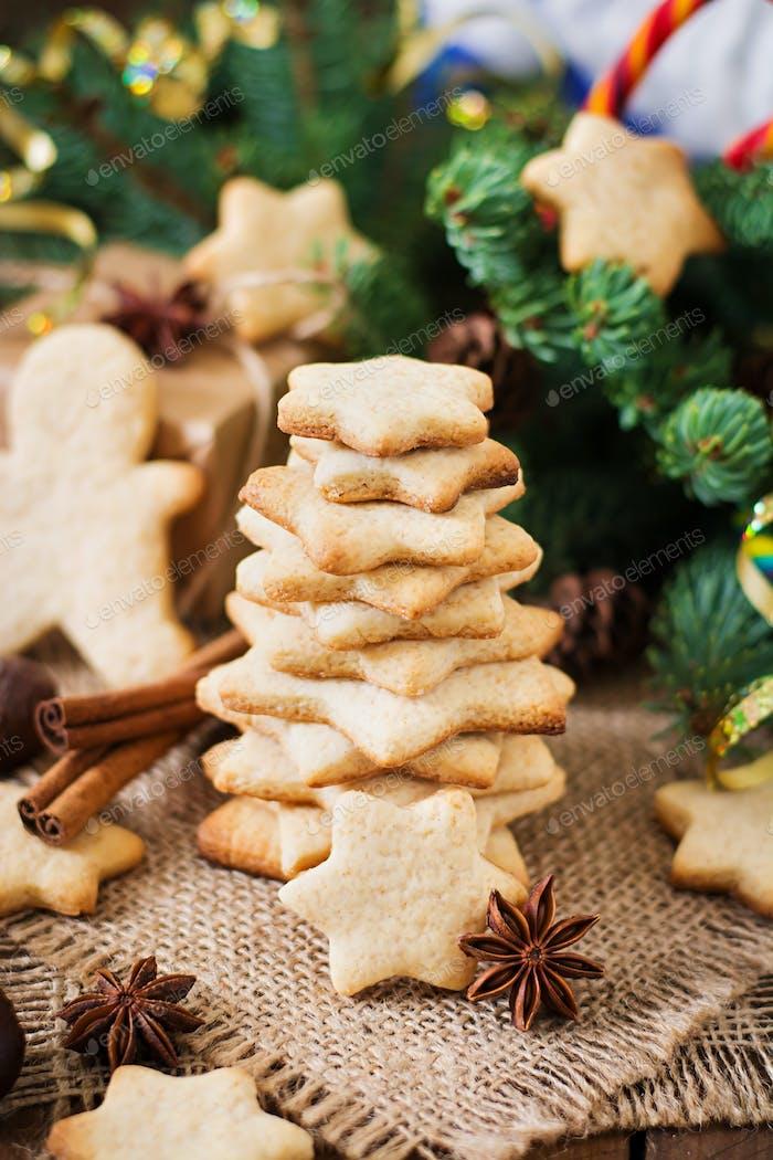 Weihnachtsplätzchen und Lametta auf dunklem Holzhintergrund