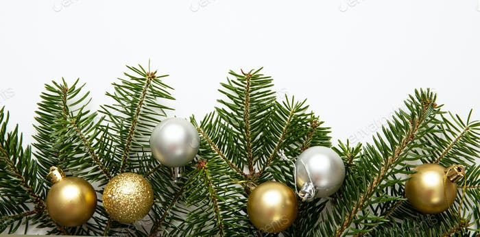Fir twig and christmas baubles, white background