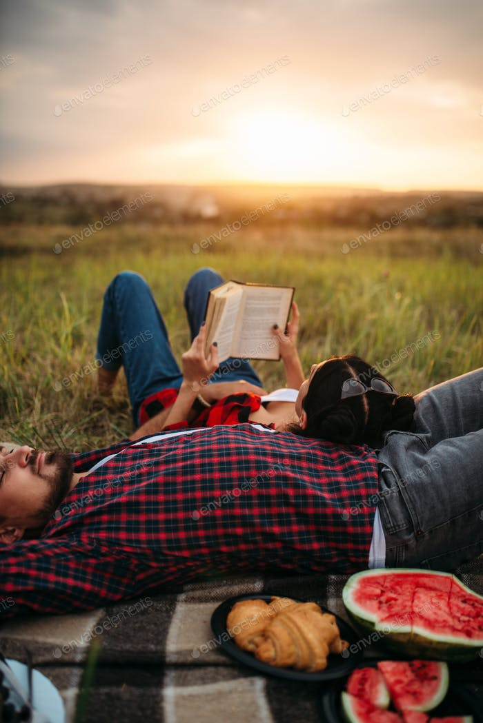 Love couple resting together, picnic in the field