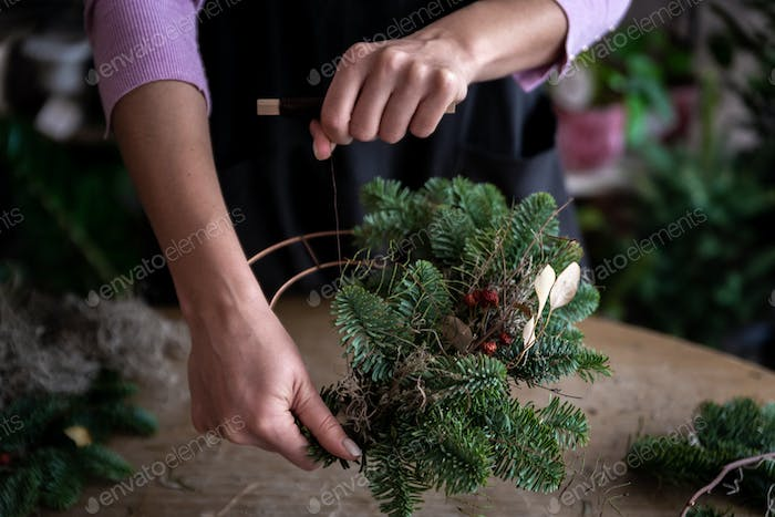 Woman making Christmas wreath of spruce, step by step.