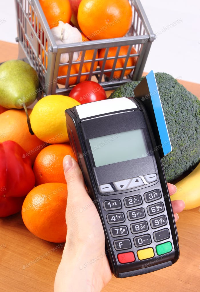 Payment terminal with credit card and fresh fruits and vegetables, cashless paying for shopping