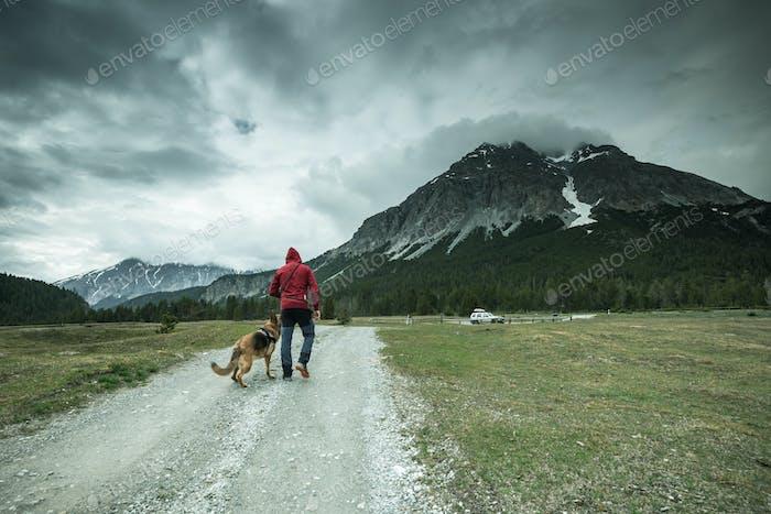 Man with dog trekking mountains in Switzerland