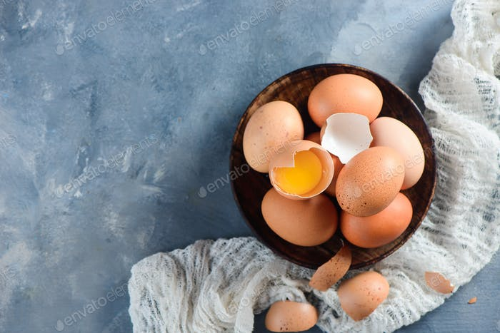 Fresh chicken eggs in a wooden bowl on a concrete background with white cloth. Organic ingredients
