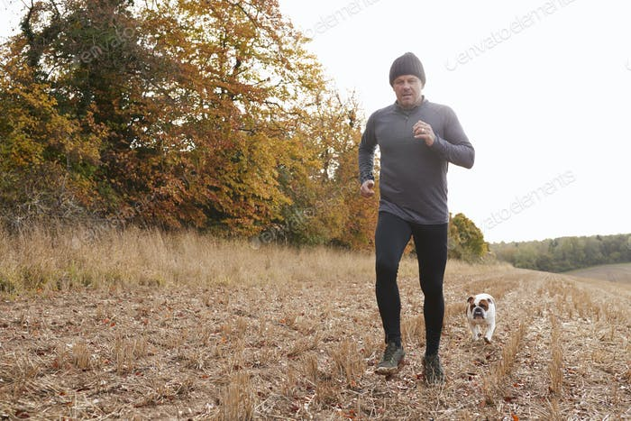 Mature Man Running Around Autumn Field With Pet Bulldog