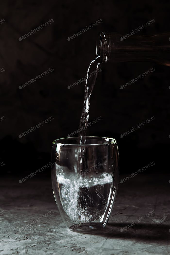 Water poured from the bottle into a glass cup on a black background