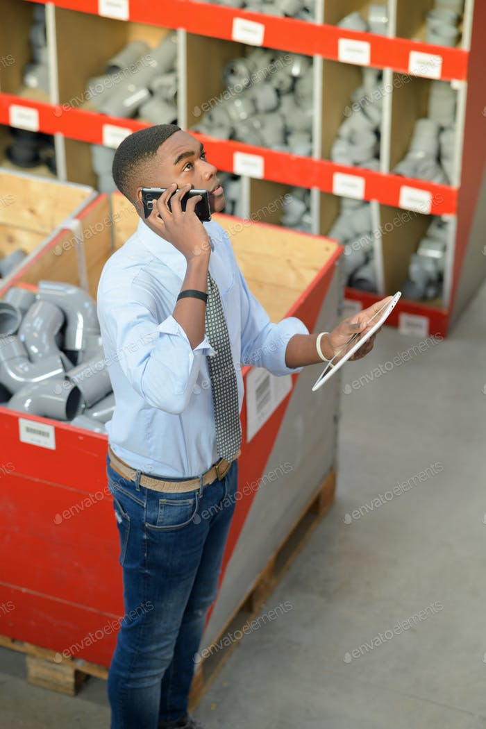 Worker on telephone in plumbing supplies shop