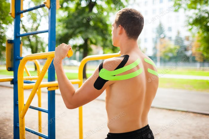 Bodybuilder with elastic tapes posing at sports ground