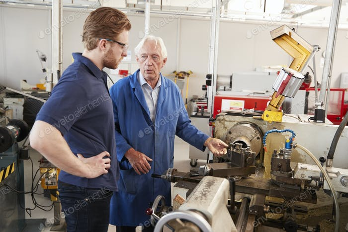 Senior engineer talking to apprentice at machine bench