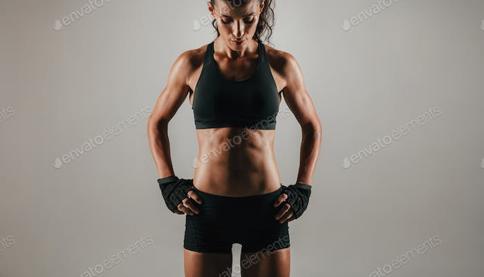 Abdominal muscles of woman over gray background
